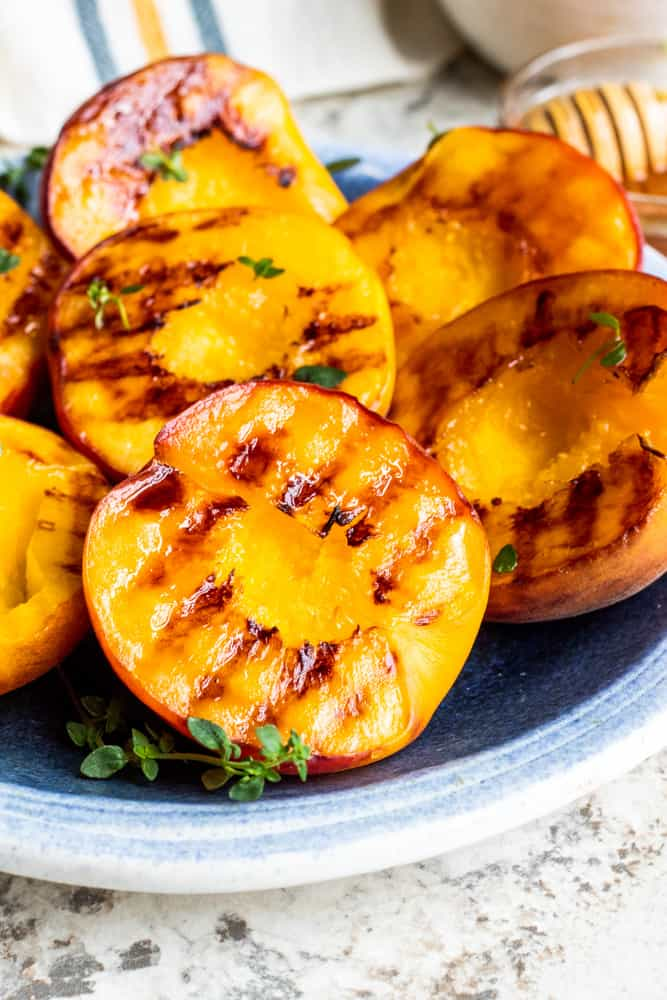This Easy Grilled Peaches Recipe with brown sugar, mascarpone, honey and fresh thyme is the best dessert, snack or appetizer for summer! This healthy, vegetarian recipe can be made out an outdoor barbecue grill, stove-top, or in the oven. {VIDEO} #glutenfree #vegetarian #peaches #nutfree #lowcarb