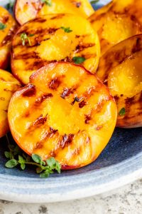 Close up shot of grilled peach on a clue plate on white counter top.