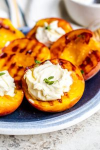 Close up of grilled peaches on a blue plate with mascarpone cheese and thyme on top.