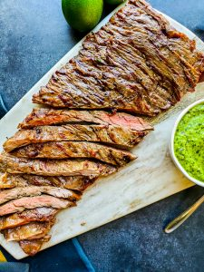 Overhead shot of partially sliced grilled skirt steak on a cutting board with chimichurri sauce.