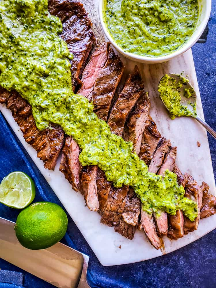This Grilled Skirt Steak recipe with Chimichurri Sauce is the best summer BBQ recipe for your family and friends! Easy how to steps and tips for tender meat perfect for tacos, fajitas, meal prep, or on its own. The marinade is packed with orange juice, olive oil, soy sauce and garlic and pairs great with so many Mexican dishes. #lowcarb #skirtsteak #BBQ #paleo #keto #food #meatrecipes #dinnerrecipes