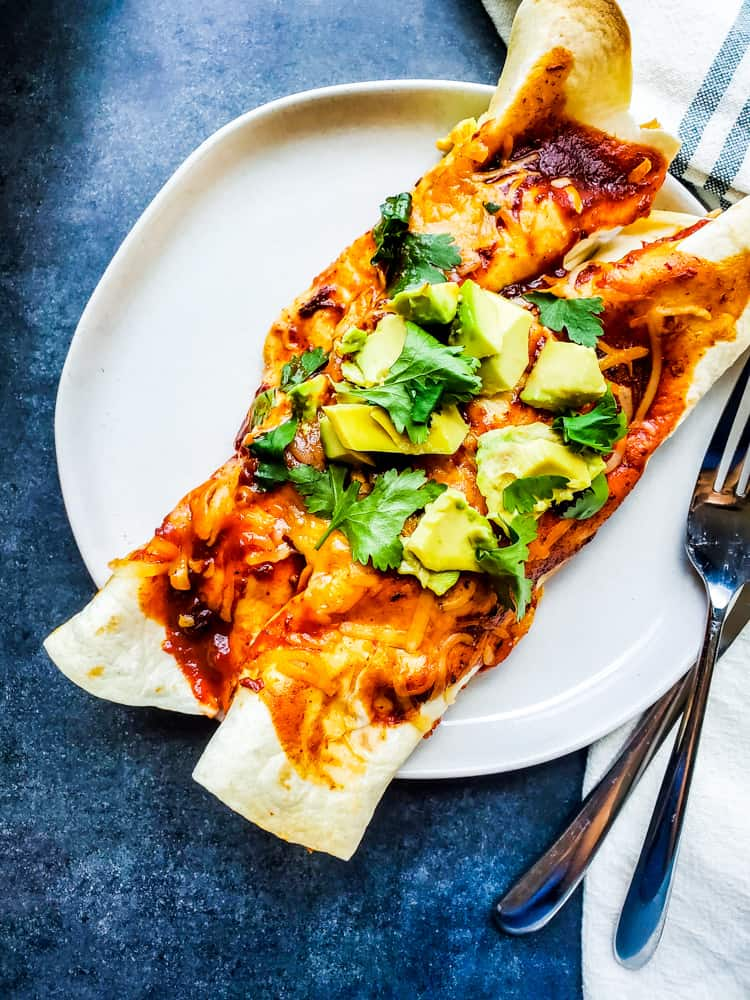 Overhead shot of two enchiladas on a white plate.