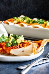 Shot of two veggie enchiladas on a white plate with silver fork and knife on the side. A white baking dish with more in the background.