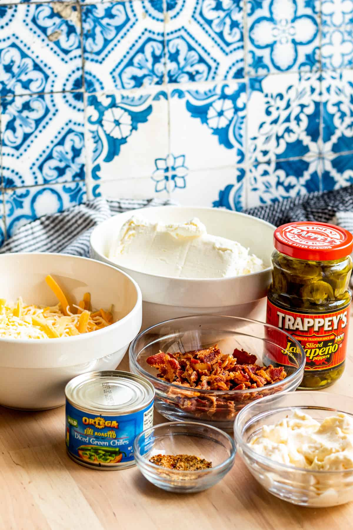 Ingredients for dip laid out on wooden table with blue and white background.
