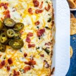 This Baked Bacon Jalapeno Popper Dip with Bacon is the best, easy appetizer recipe! Perfect for game days, parties, holidays or just for the family and ready in only 30 minutes. Pair with tortilla chips, Ritz Crackers or Veggie Sticks for the perfect finish. Simple step by step instructions for crockpot and oven, recipe alterations, and video included!
