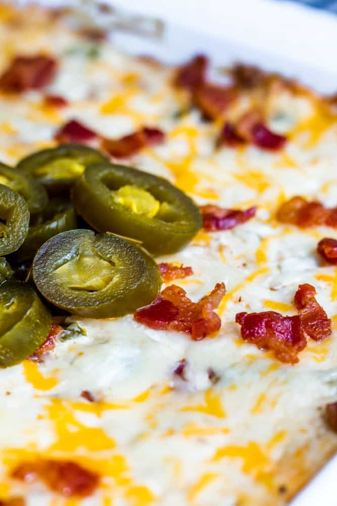 Close up shot of jalapenos on top of dip in a white dish.