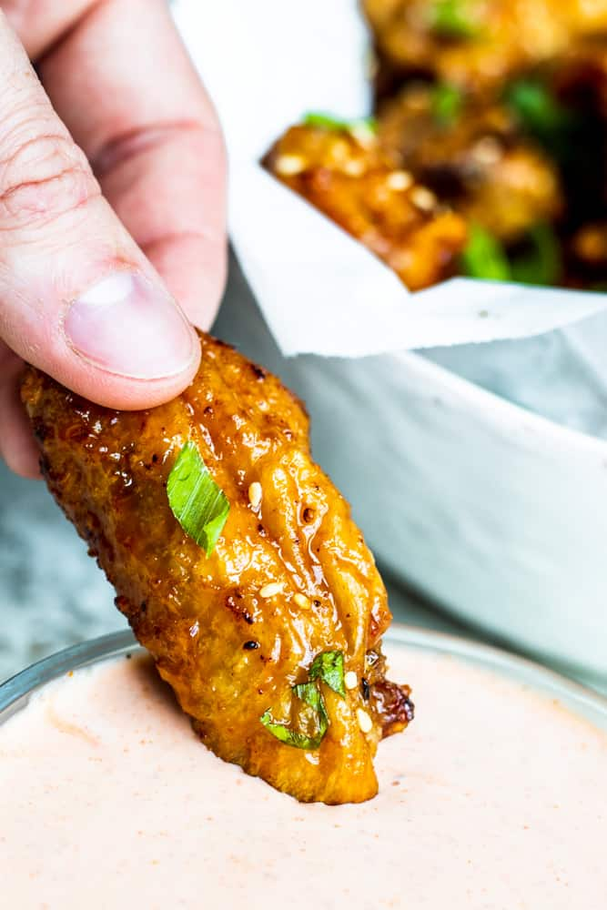 Hand dipping wing into ranch sauce with white bowl of wings in the background.