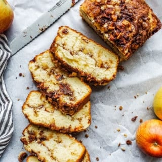 Apple bread laid out on white parchment paper and partially sliced.