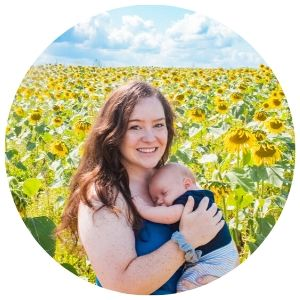 mom holding son with sunflowers in the backround.