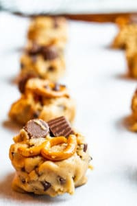 Peanut butter cookie dough on a cookie sheet in a line.