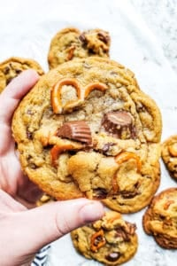 Hand holding up peanut butter pretzel cookie.