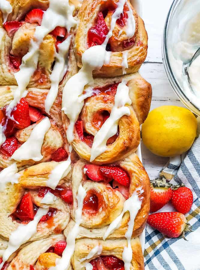 Overhead shot of strawberry rolls in a large baking dish on a white counter with bowl of icing next to it.