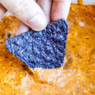 Hand dipping chip into chili cheese dip.