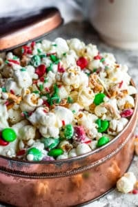 Christmas Crunch popcorn in a copper tin with lid resting on side on a white counter.