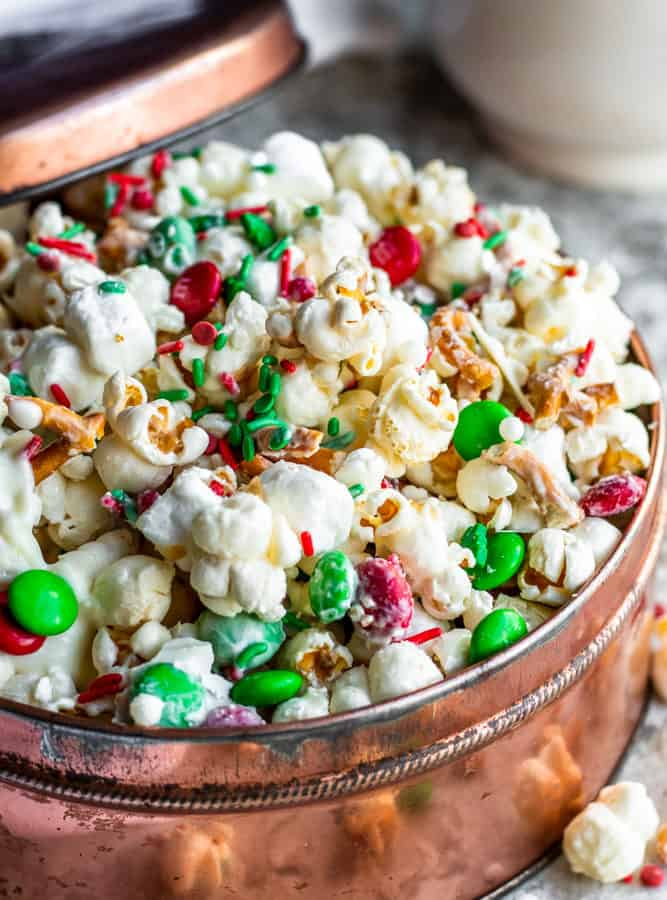 Popcorn snack mix in a copper tin on a white counter.