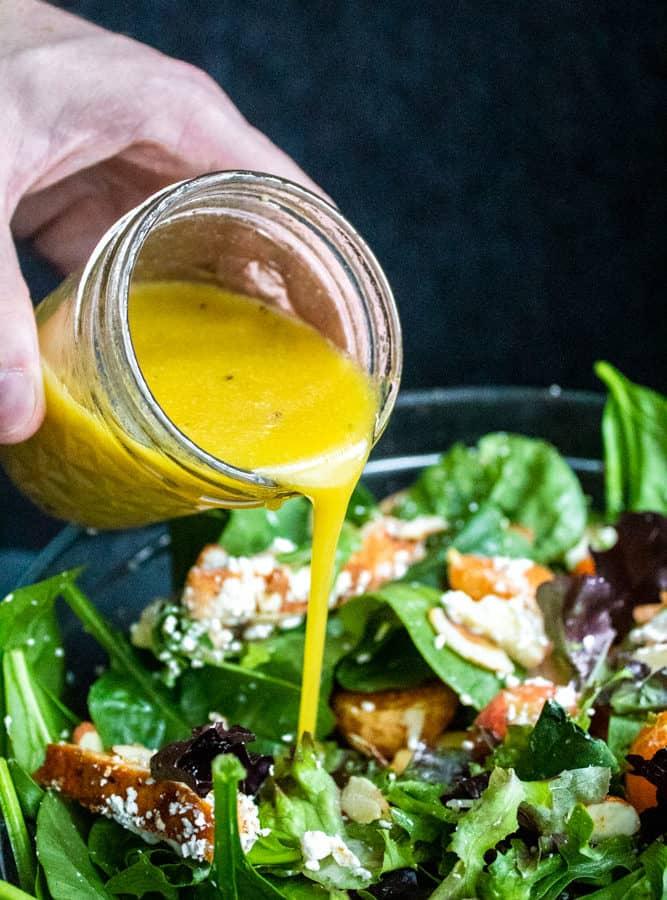 Honey Dijon Vinaigrette dressing being poured onto a bowl of salad.