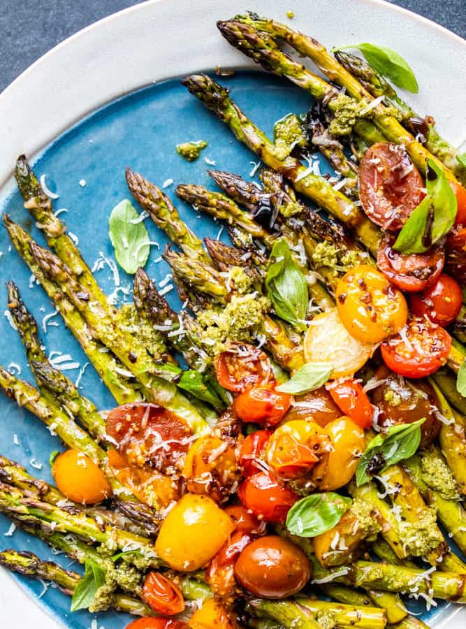 Overhead shot of asparagus on a blue and white plate on blue counter.