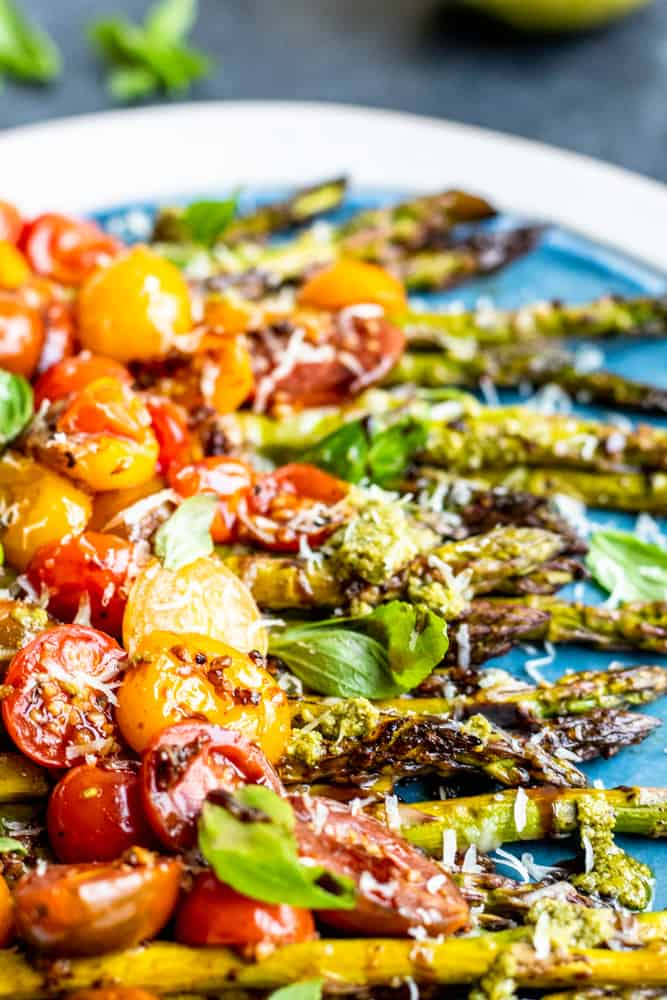 Close up shot of cooked tomatoes on top of oven roasted asparagus recipe on a large serving dish.