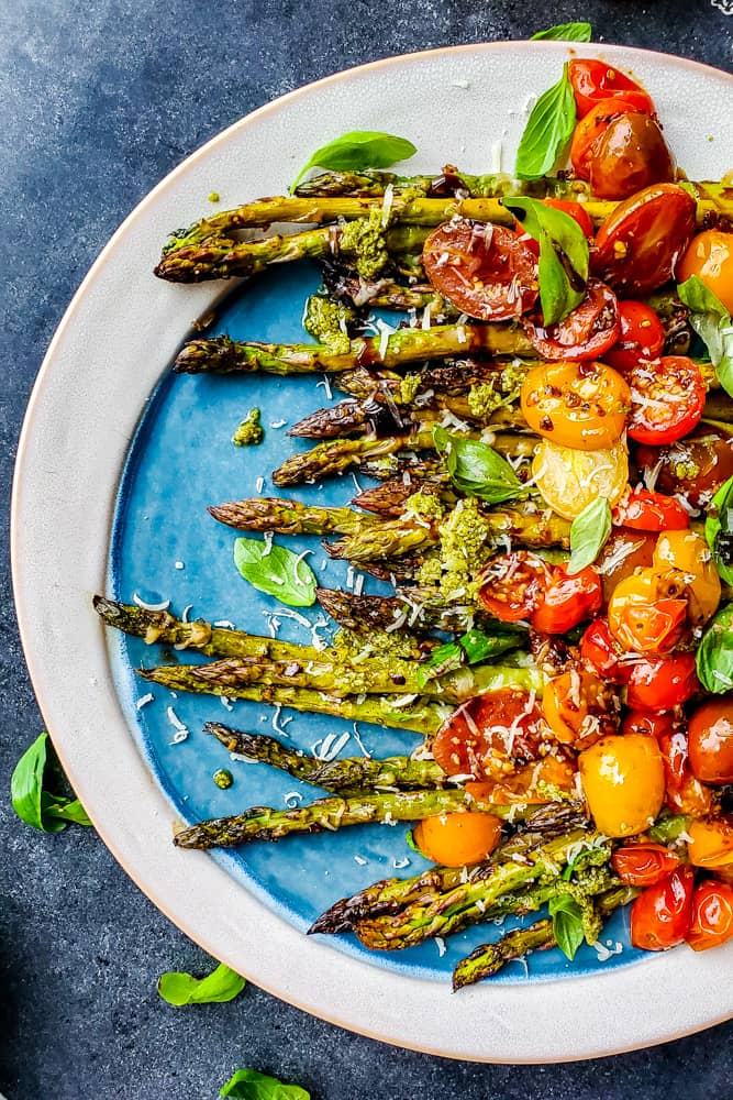 Over head shot of asparagus with tomatoes on a blue and white serving dish.