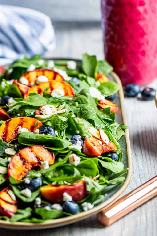 Grilled peach salad on a platter with pink dressing in the background.