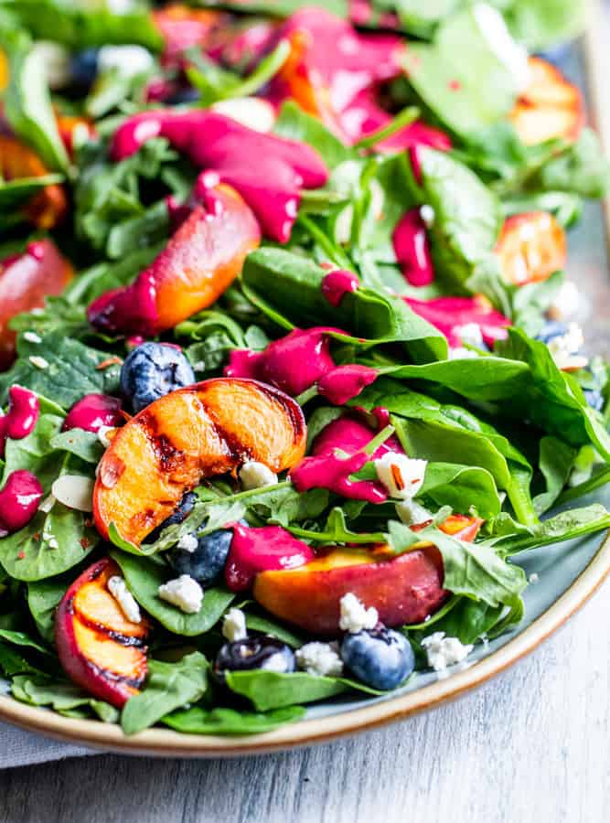 Grilled peach salad on a platter on a white counter.