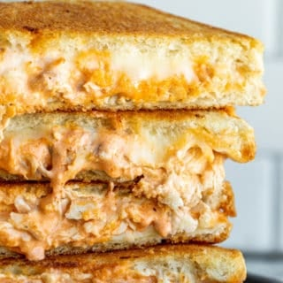 Stack of grilled cheese on black plate.