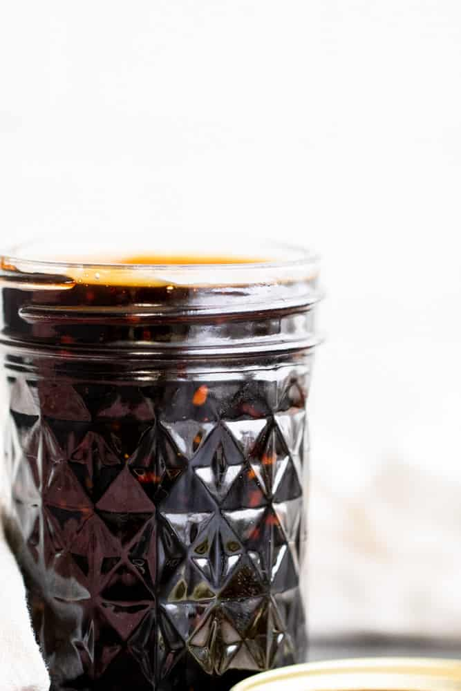 Strait on shot of teriyaki sauce in a glass mason jar with white background.