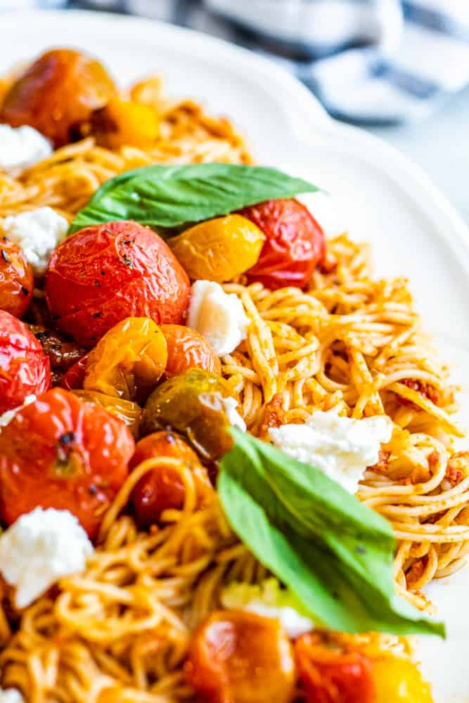 Close up of roasted tomatoes on top of pasta.