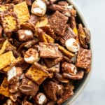 Overhead shot of snack mix in a bowl on a white counter.