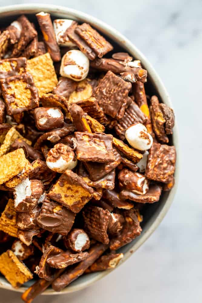 Overhead shot of s'mores snack mix in a white bowl on a white counter.