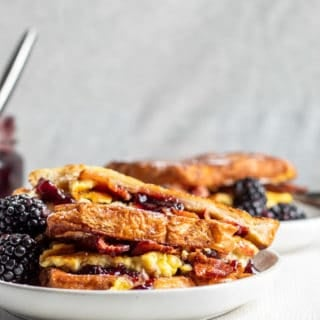 French toast sandwich on a white plate with gray background and second plate in the background.