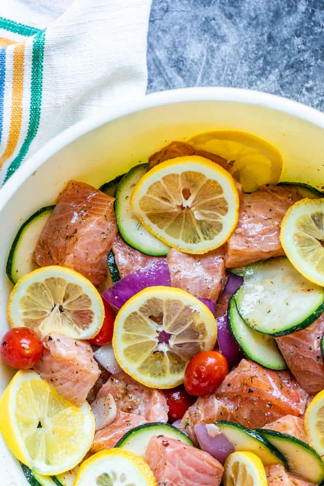Salmon and cut veggies marinading in a large bowl on a blue counter.
