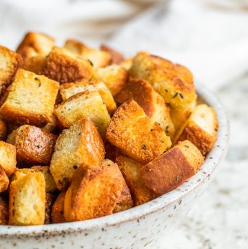 Croutons in a white bowl on a white counter.
