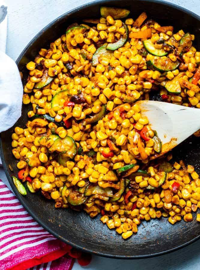 Warm corn salad in a black skillet.