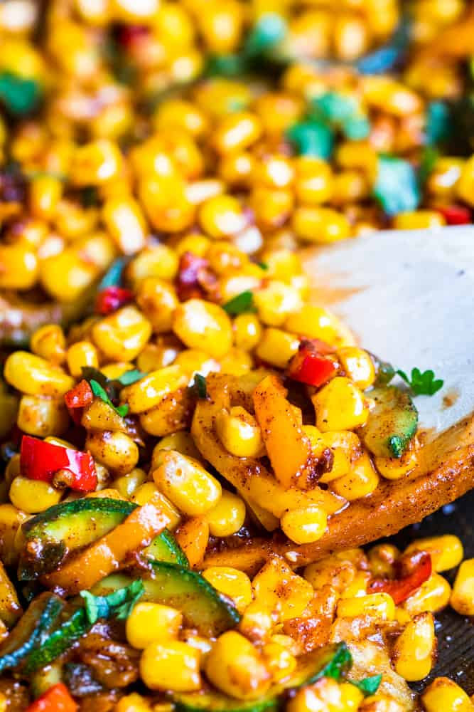 Wooden spoon scooping up corn and pepper salad recipe.