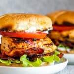 Strait on shot of chicken sandwich on white plate on white counter.