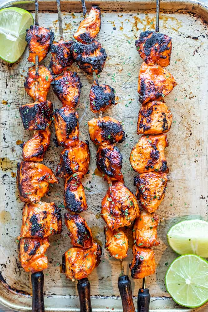 Overhead shot of chicken skewers on a metal sheet with sliced limes.