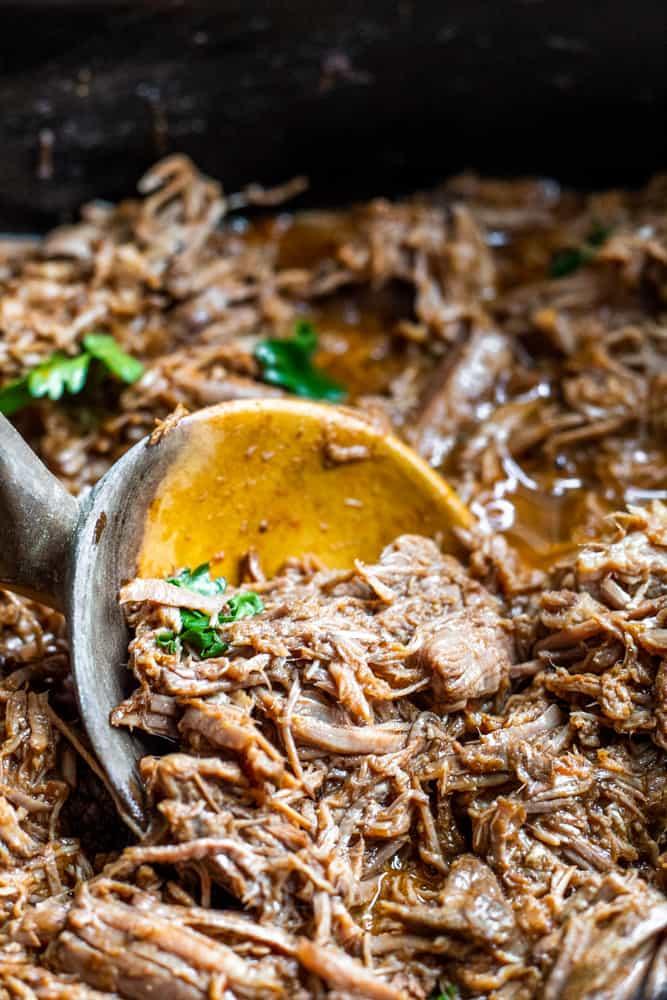 Wooden spoon scooping up beef in crockpot.