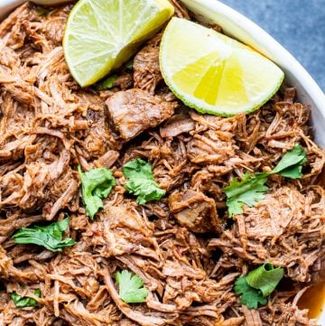 Overhead shot of shredded beef in a large white bowl on blue counter.