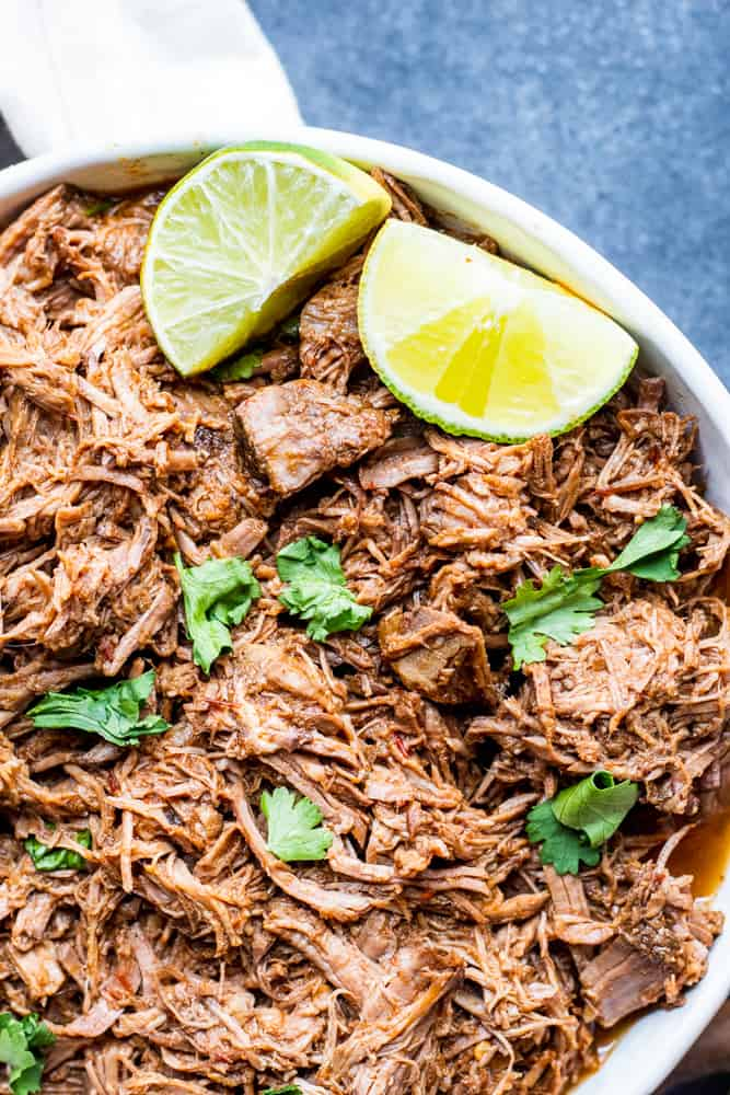Overhead shot of beef barbacoa in a large white bowl on a blue counter.
