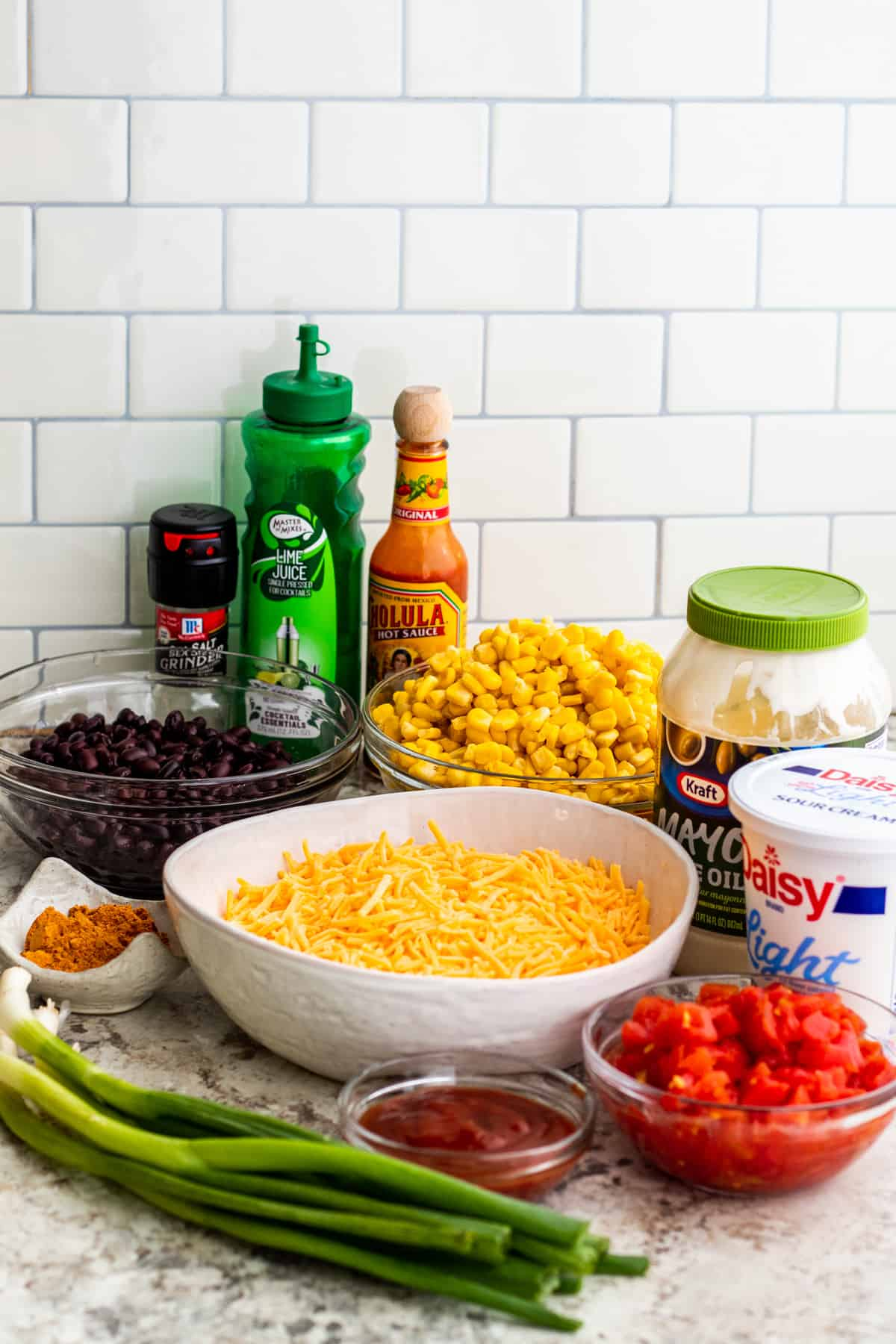 Ingredients for dip in bowls and containers laid out on white counter.