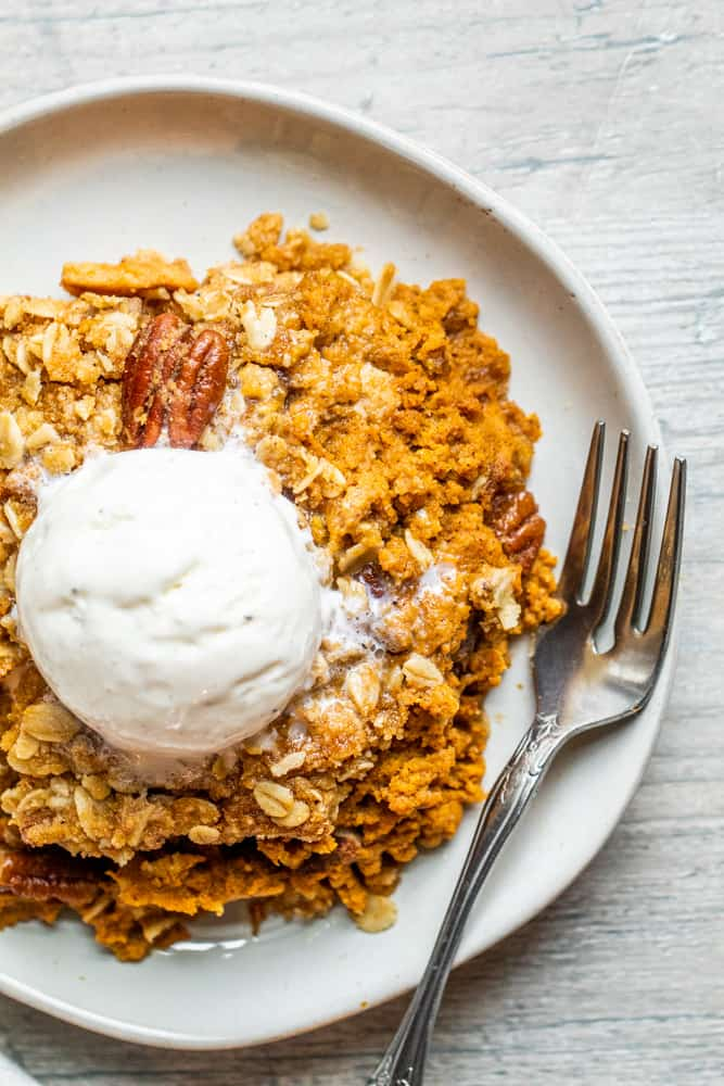 Overhead shot of pumpkin crisp on a white plate with a silver spoon.
