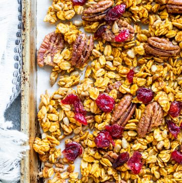 Overhead shot of pumpkin spice granola on a tray with towel.