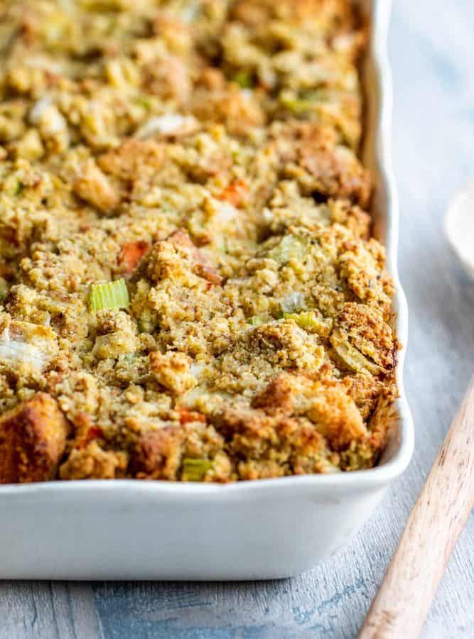 Cornbread dressing in a white baking dish with wooden spoon on the side.