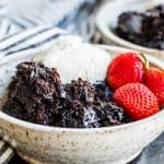 Chocolate lava cake in a white bowl with strawberries and ice cream.