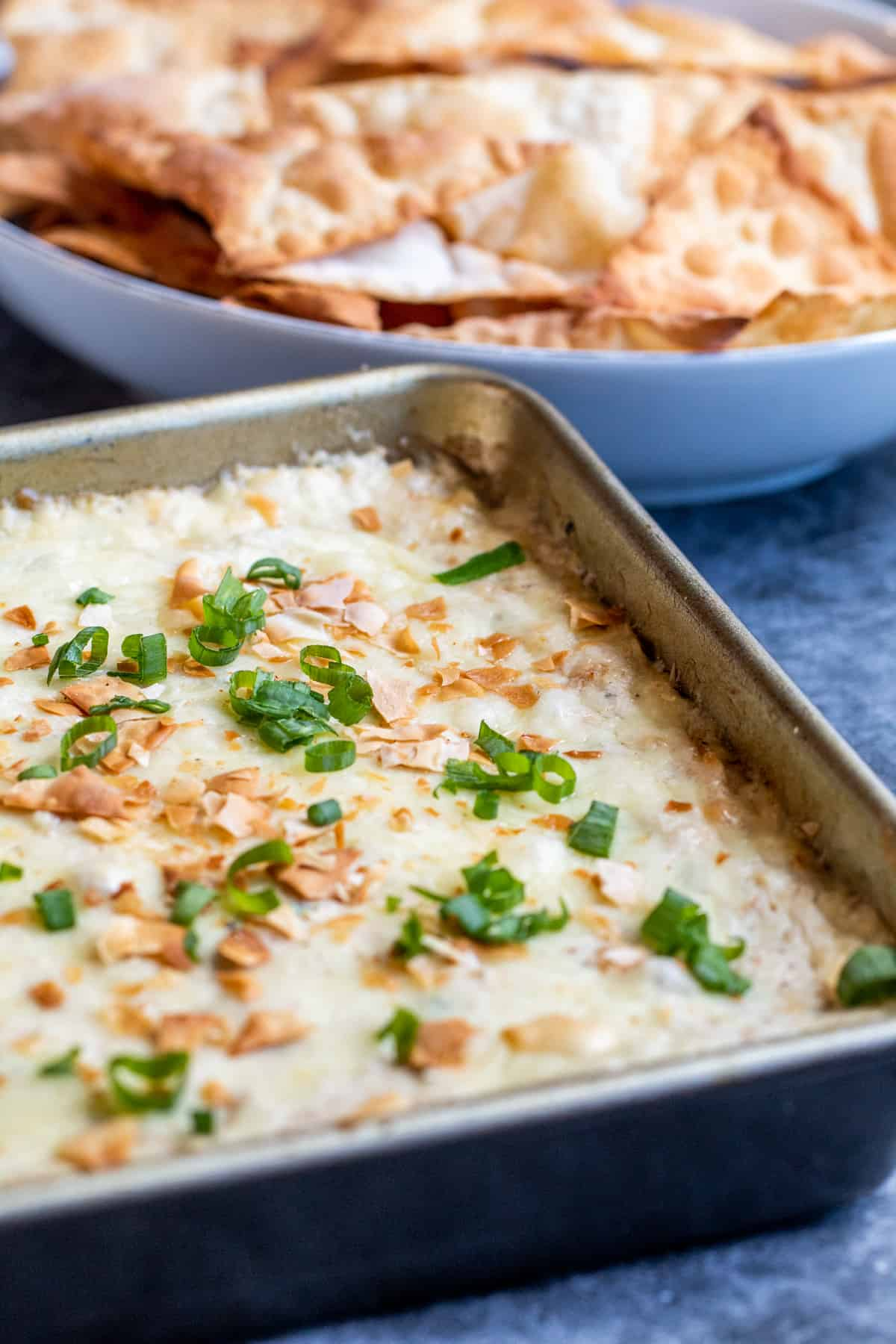 Crab dip in a baking pan on a blue counter with chips in the background.