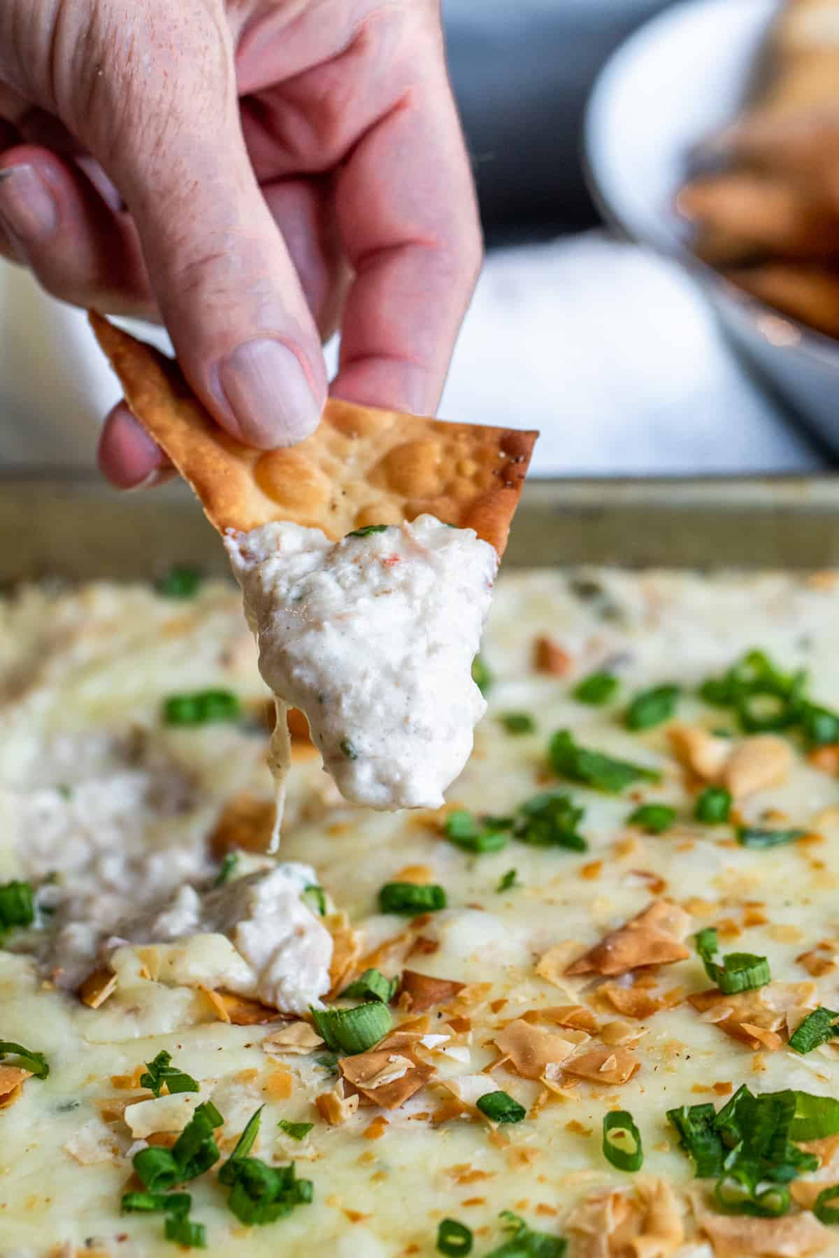 Hand dipping wonton chip into dip.