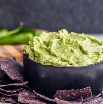 Angle shot of creamy guacamole in a black bowl with chips.