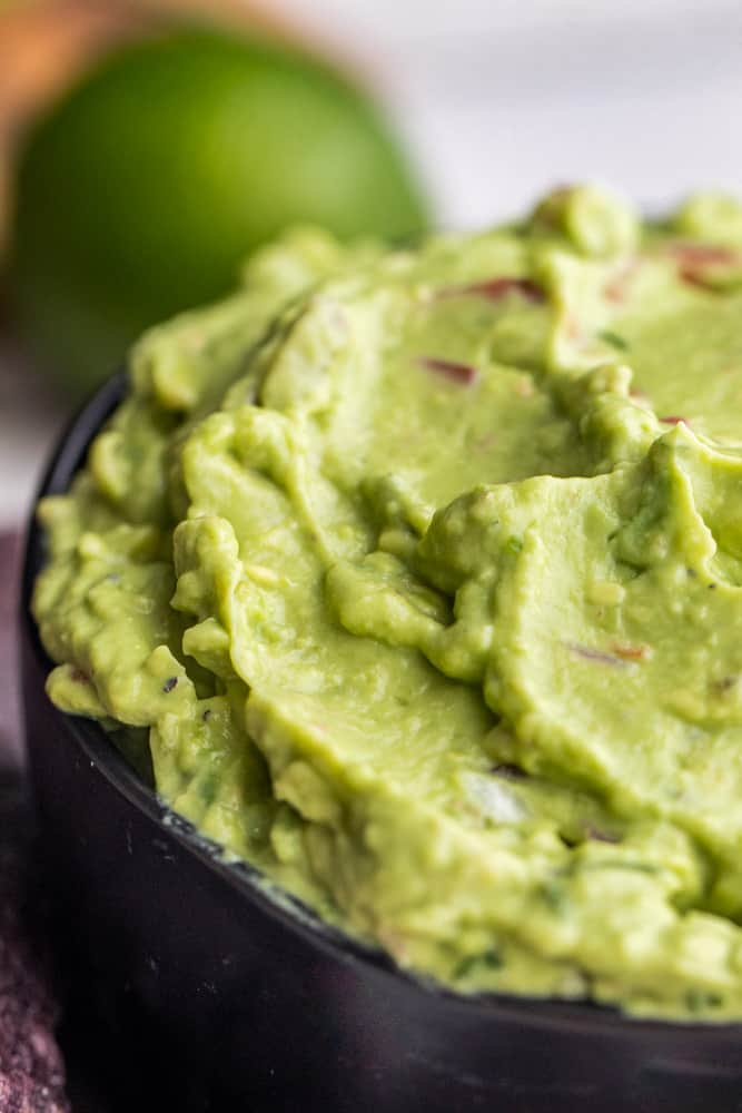 Close up image of guacamole dip in black bowl.