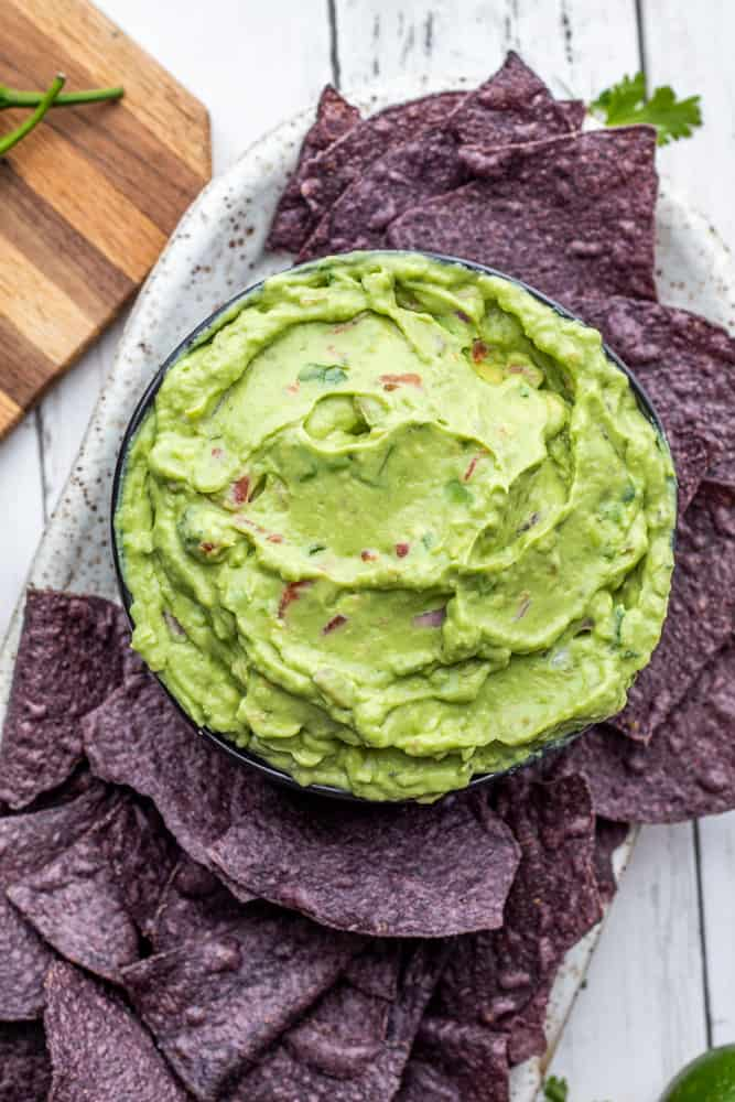 Overhead shot of guacamole in black bowl with blue chips on a white counter.